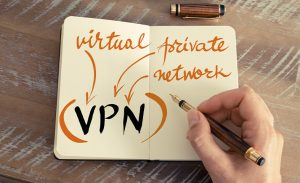 an image of a person writing the words vpn with a pen on a notebook