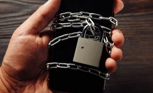 a person holding a smartphone with a literal lock on it