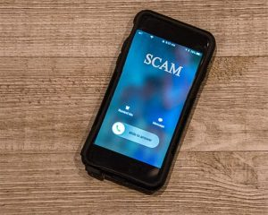 An image of a phone while somebody is calling him and it says scam representing a spam call