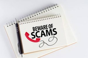 An image featuring notebooks and a pen with text on it that says beware of scams