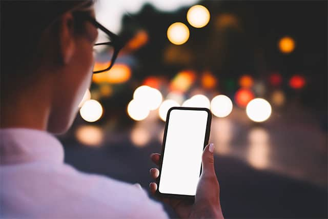 An image featuring a person holding out his Android phone while using an anonymous chat application