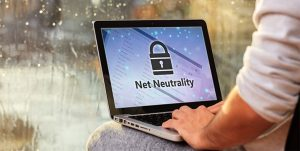 An image featuring a person using their laptop that says net neutrality on it