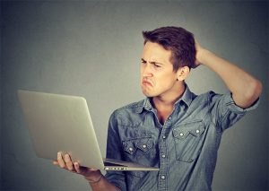 An image featuring a person that is holding his laptop and is confused because of weird software