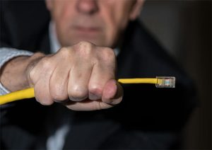 An image featuring a person holding a cable in his hand representing regulations concept