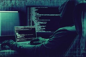 An image featuring a person wearing a hoodie and hacking on his laptop and PC representing a hacker