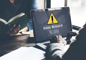 An image featuring a person using his laptop that says data breach on it