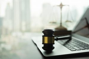 An image featuring a laptop with a gavel on top of it representing the internet privacy law concept