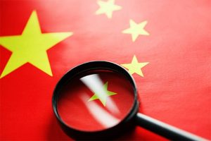 An image featuring the China flag with a magnifying glass representing surveillance state