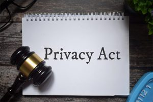 An image featuring a gavel on top of a notebook that says privacy act on it