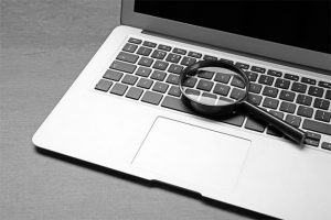 An image featuring a laptop with a magnifying glass on top of it