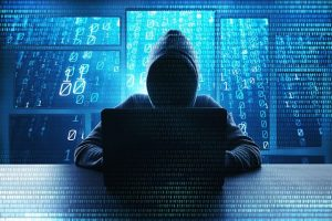 An image featuring a person wearing a hoodie representing a hacker and using his laptop