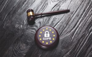 An image feautring a gavel and a circle with start that has a lock in the middle and says GDPR representing GDPR concept
