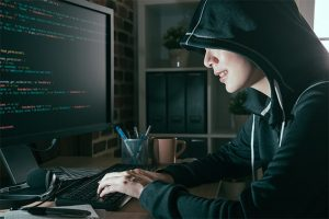 An image featuring a person wearing a hoodie and hacking representing invasion of privacy concept