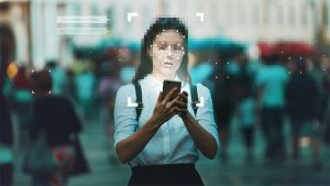 An image featuring a person holding her phone while her face is blurred representing privacy of the body concept