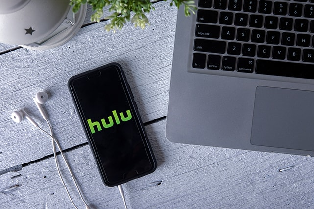 An image featuring a phone connected with earphones and a laptop next to it while the phone has Hulu opened on it