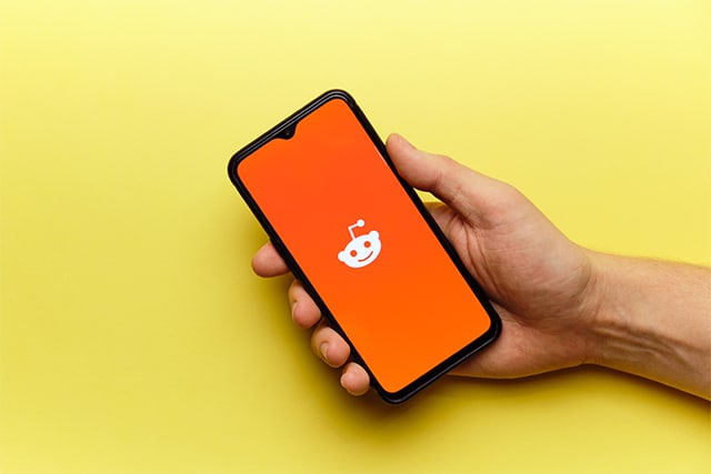 An image featuring a person holding his phone that has Reddit opened with yellow color background