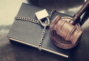 An image featuring a book that is locked with gavel on top of it representing privacy freedom concept