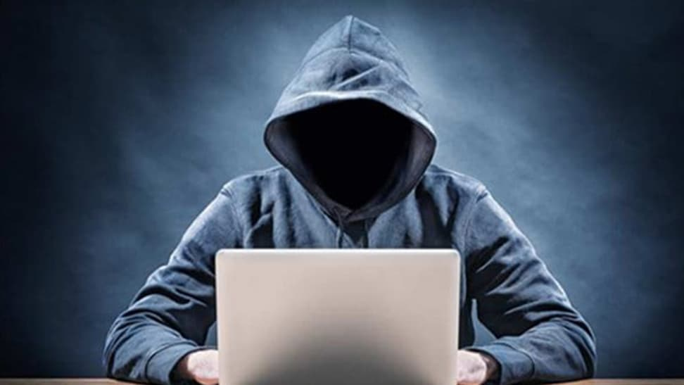 an image of a person sitting on a laptop with a hoodie