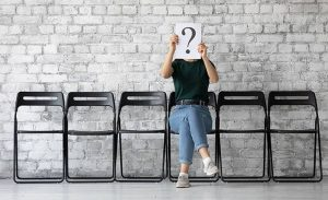 Anonymous young woman sit on chair hiding her face behind paper with interrogation symbol